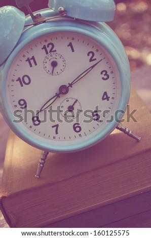 Vintage turquoise clock on book  - stock photo