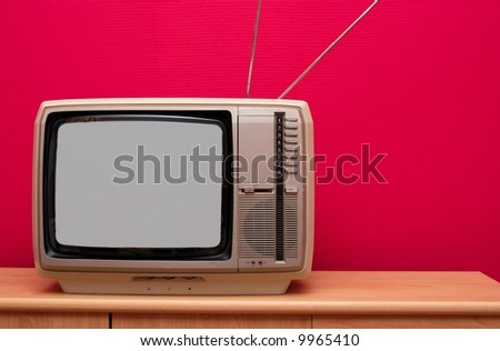 Vintage TV in a room with red wall - stock photo