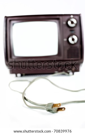 Vintage TV on white background close-up. Focus is on the plug laying in front of the TV. - stock photo