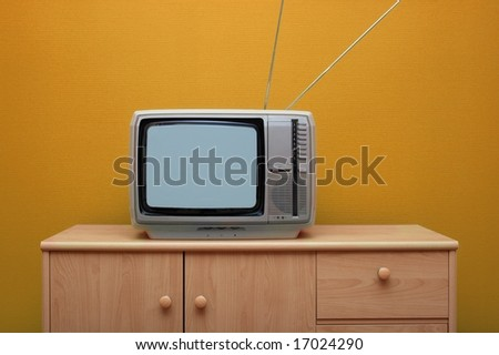 Vintage TV set, orange wall - stock photo