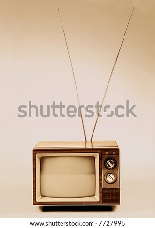 Vintage TV with antenna over a sepia background. - stock photo