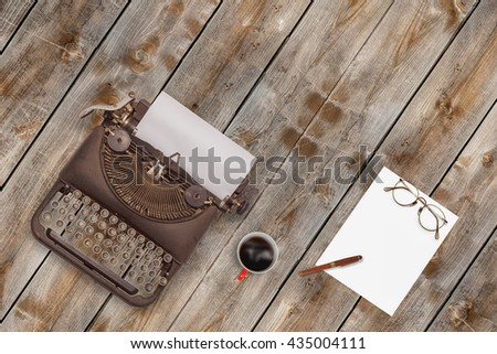 Vintage typewriter and coffee on wood background