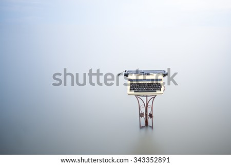 Vintage typewriter isolated on sea water background concept - stock photo