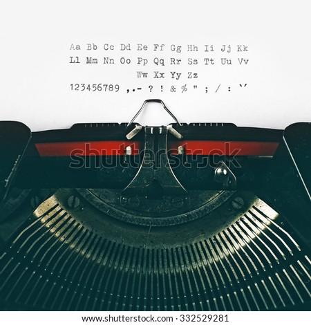 Vintage typewriter machine typeset alphabet, numbers and symbols on white paper. - stock photo
