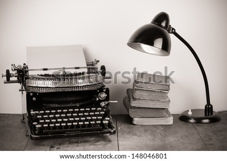 Vintage typewriter, old books and retro lamp on table - stock photo