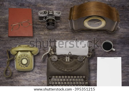 Vintage typewriter ,old clock and old camera on wood background  - stock photo