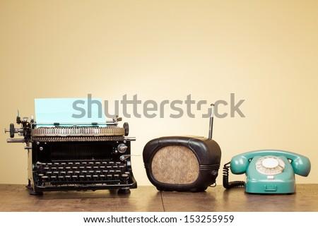 Vintage typewriter, old radio, retro telephone on wood table - stock photo