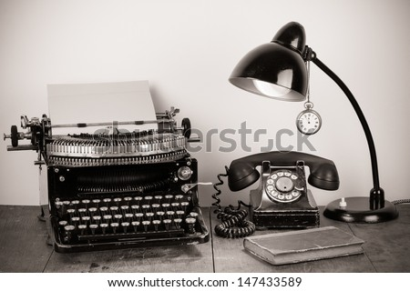 Vintage typewriter, old rotary telephone, lamp, book, pocket watch on table still life - stock photo