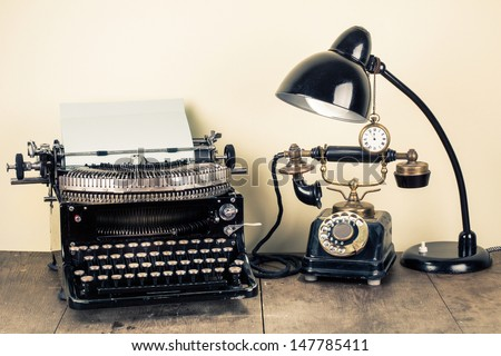 Vintage typewriter, old rotary telephone, table lamp, pocket watch still life - stock photo