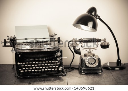 Vintage typewriter, old rotary telephone, table lamp still life - stock photo