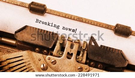 Vintage typewriter, old rusty, warm yellow filter, breaking news - stock photo