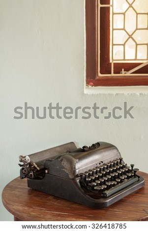 Vintage typewriter on an old desk - A vintage typewriter in working condition sits unused on an old desk. - stock photo