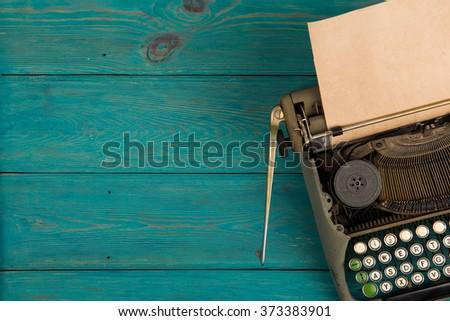 Vintage typewriter on the blue wooden desk  - stock photo
