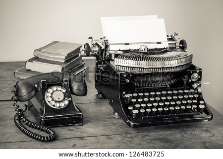 Vintage typewriter, telephone, old books on table desaturated photo - stock photo