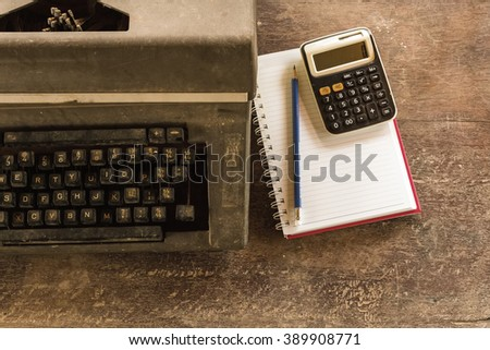 Vintage typewriter ,white  book, calculator ,pencil and candlelight on old wooden touch-up in still life concept