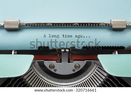 "Vintage Typewriter With Phrase ""A long time ago..."" Typed in Blue Paper - stock photo"
