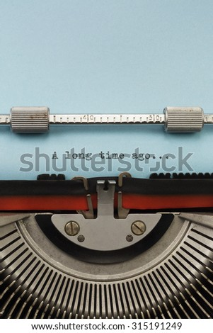 "Vintage Typewriter With Phrase ""A long time ago"" Typed on Blue Paper Vertical Photograph - stock photo"