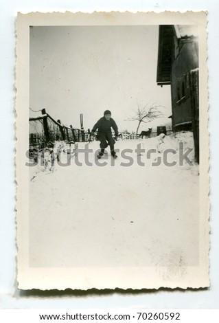 Vintage unretouched photo of boy skiing - stock photo