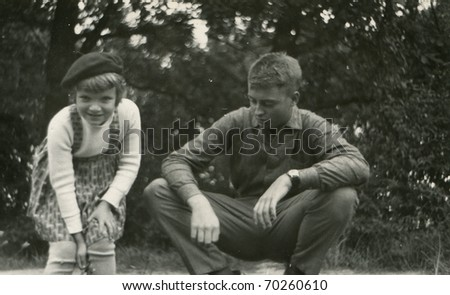 Vintage unretouched photo of brother and sister playing outdoor - stock photo