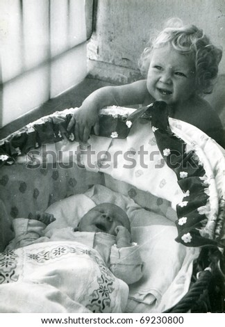 Vintage unretouched photo of little girl with her newborn brother - stock photo