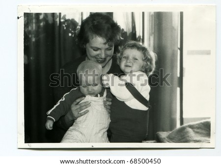 Vintage unretouched photo of young children with their mother - stock photo