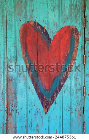 Vintage Valentine heart on a weathered wooden door.  - stock photo