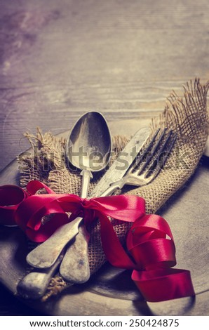 Vintage valentine table settings decorated with red ribbon. Image is filtered. - stock photo