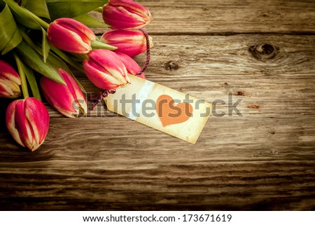 Vintage Valentines or anniversary gift with an aged yellow gift tag or label with a red heart attached to a bouquet of fresh red tulips on a weathered rustic wooden background with copyspace - stock photo