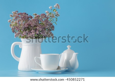 Vintage Vase with a bouquet of blossoming oregano on plain blue background - stock photo