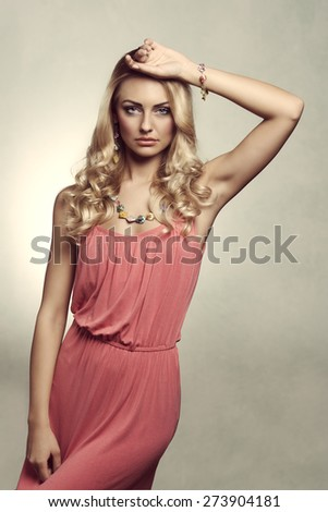 vintage version of summer blond young woman , with color dress , and jewellery. She is posing on grunge background - stock photo