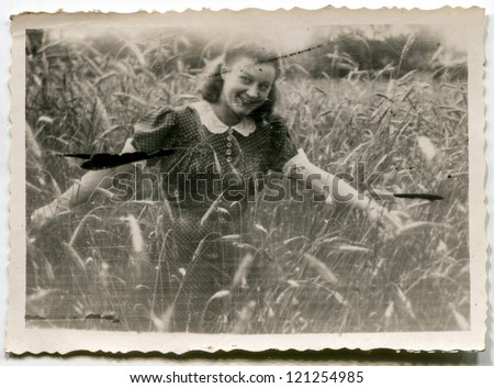 Vintage very grunge photo of young woman in wheat (forties) - stock photo