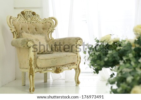vintage victorian chair and flower composition of white roses on the floor vase