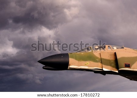 Vintage Vietnam era fighter plane with pilot and navigator seems to be flying into ominous thunderstorm - stock photo