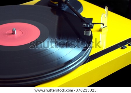 Vintage vinyl LP record with red label sound reproduction on vintage turntable record player with yellow case isolated on black background. Horizontal photo diagonal view closeup - stock photo