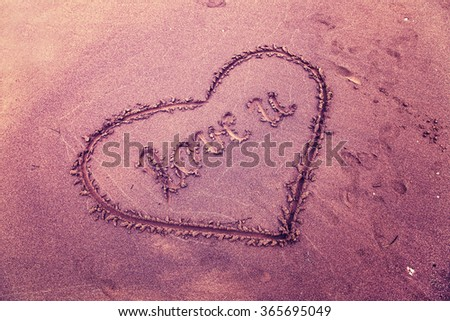 Vintage violet color hand drawn heart symbol with handwritten love you alphabet on the beach sand.  Retro color filter effect used. - stock photo