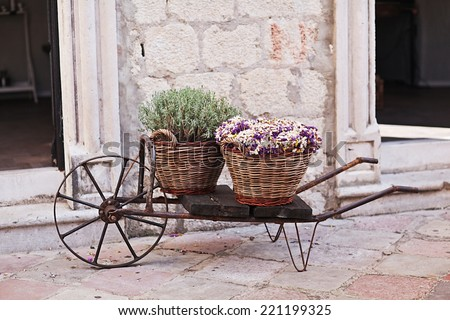 Vintage wagon with basket with lavender flowers near the old wall - stock photo