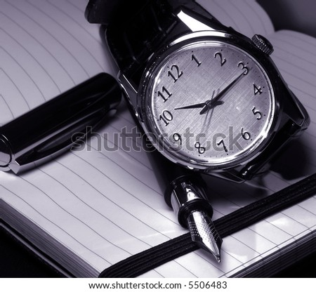 vintage watch and pen over notebook - stock photo