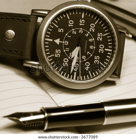 vintage watch and pen over notebook selective focus on watch monochrome image