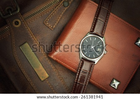 Vintage watch on a brown leather wallet. Classic Wristwatch. (Vintage Style Color Process) - stock photo