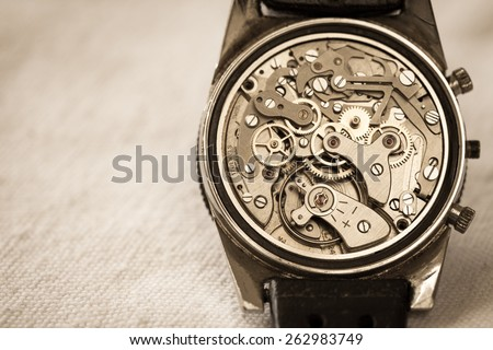 Vintage watch showing it's complex movement and parts. In sepia tone for mood. - stock photo