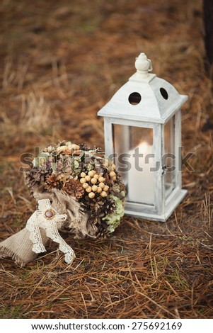 Vintage wedding bouquet and wooden lantern with candle - stock photo