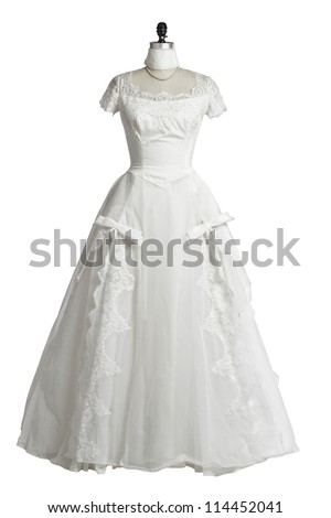 Vintage wedding dress of ivory tulle over satin with empire neckline, lace cap sleeves, princess waist, and fitted bodice. Displayed upright on stand. White background, cut out, vertical, copy space. - stock photo
