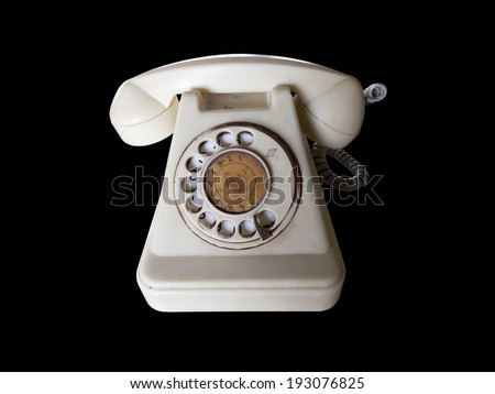 Vintage white bell system rotary telephone isolated on black. - stock photo