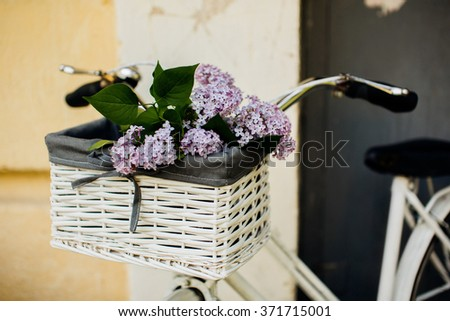 Vintage white bicycle with beautiful flowers in the basket - stock photo