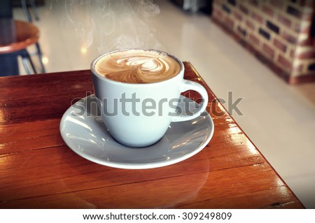 vintage white cup of hot coffee on wooden in coffee shop