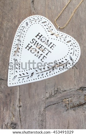 Vintage white heart, text home sweet home, on rustic wood background - stock photo