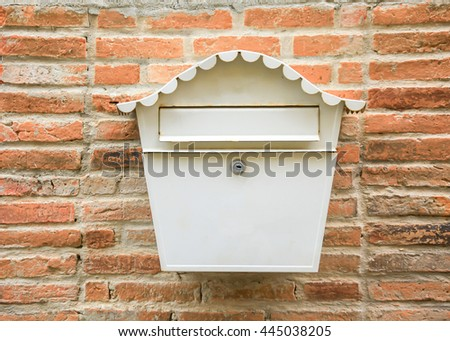 Vintage white mail box hanging on red brick wall - stock photo