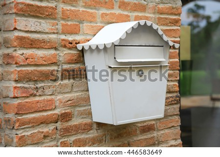 Vintage white mail box hanging on red brick wall (selective focus). - stock photo