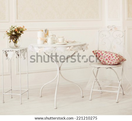 vintage white room with chair and table with flowers pillow, coffee cups and candles - stock photo