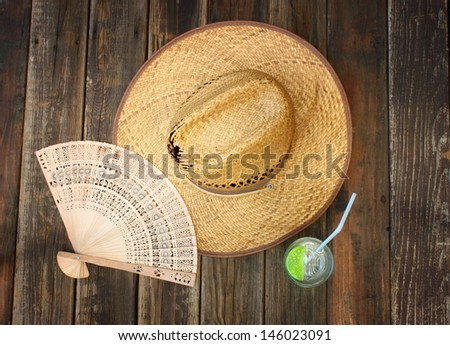 vintage wicker hat, folding fan and cold drink on wooden table - stock photo